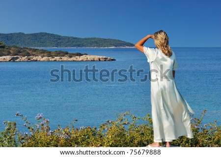 A blond beautiful woman is gazing at the spectacular view of the Greek islands during a clear morning of her summer holidays - stock photo