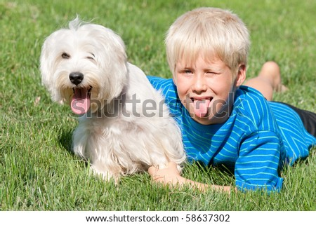 A blond boy and his white dog are lying on the green meadow with their pink tongues out