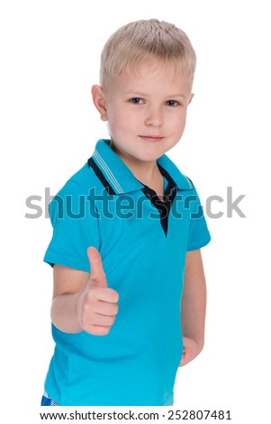 A blond boy holds his thumb up on the white background