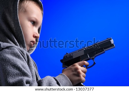 a blond boy is holding a gun on blue