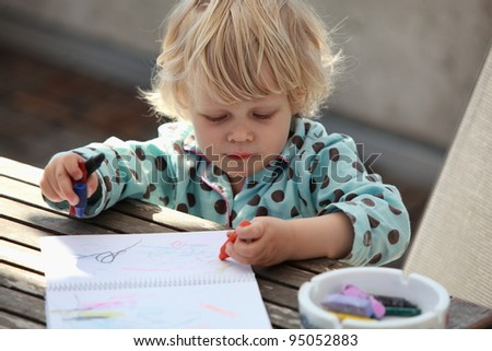 A blond Caucasian girl child  drawing an abstract picture with a  crayons  at a table in the backyard - stock photo