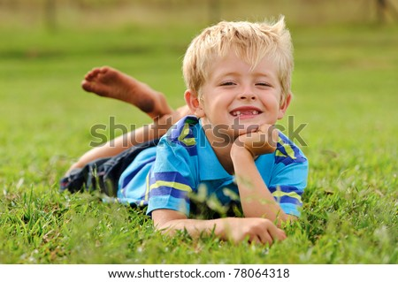 A blond child lies on some grass on a summer day