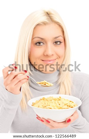 A blond female eating cornflakes at breakfast isolated on white background