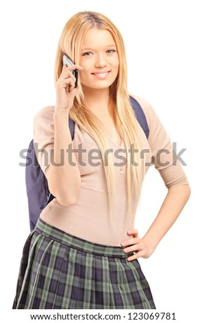 A blond female student with a school bag talking on a cell phone isolated on white background - stock photo