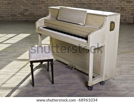 A blond finished upright piano in an old empty factory