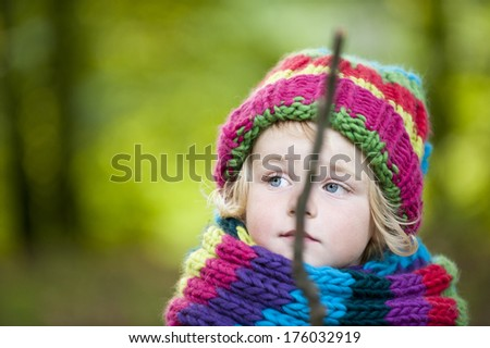 A blond girl in a large knit hat and scarf. - stock photo