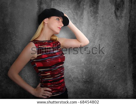 A blond girl is holding her black hat and looking to the side. The wall behind her is textured and black. Use it for a nightclub or culture concept. - stock photo