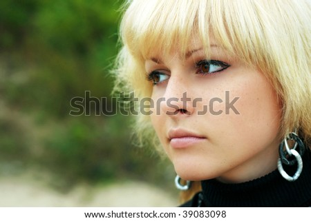 a blond girl looks in distance, nature - stock photo