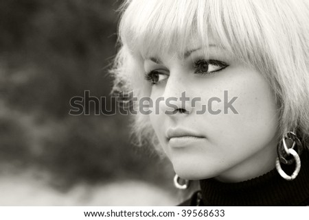 a blond girl looks in distance, nature, B&W - stock photo
