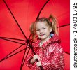 A blond girl with a red umbrella and raincoat. - stock photo