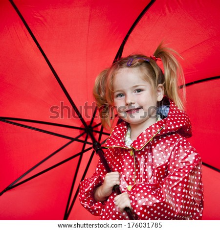 A blond girl with a red umbrella and raincoat.