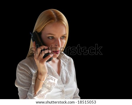 A Blond is on the phone against a black background. She looks worried or scared. - stock photo