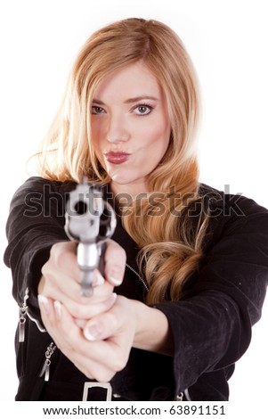 A blond is pointing a gun with a big smirk on her face. - stock photo