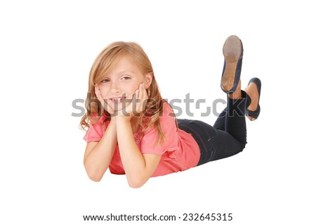 A blond little girl in a pink sweater lying on the floor on her stomach, smiling, isolated on white background.  - stock photo