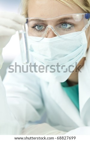 A blond medical or scientific researcher or doctor looking at a test tube of clear solution in a laboratory or hospital - stock photo