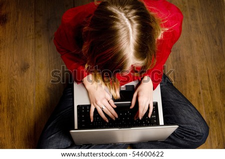 a blond teenager girl writing on her laptop - stock photo
