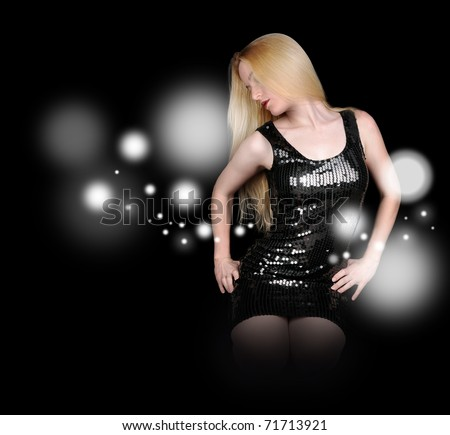 A blond woman is against a black background wearing a dress. Sparkles are surrounding her.