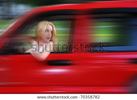 A blond woman is driving a car with a zoom speed effect. She is turning her head and not looking at the road. - stock photo
