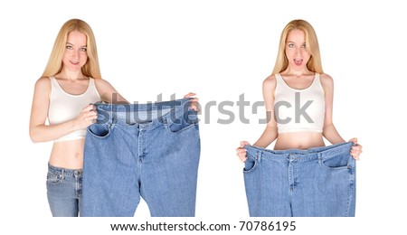 A blond woman is holding a large pair of jeans for a body makeover. She has lost weight and is on a white, isolated background. - stock photo