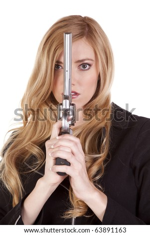 A blond woman is looking around a gun. - stock photo
