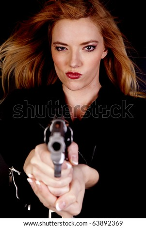 A blond woman is looking down a gun and has a serious expression on her face. - stock photo