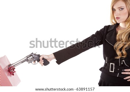 A blond woman is pointing a gun at a present. - stock photo
