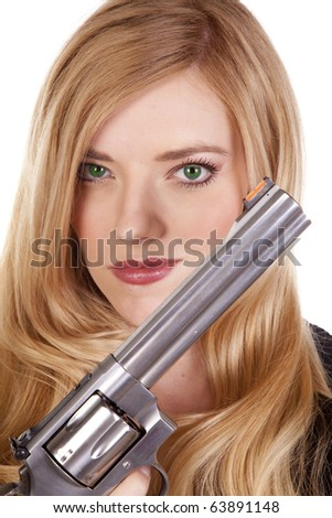 A blond woman with green eyes is holding a pistol by her face. - stock photo