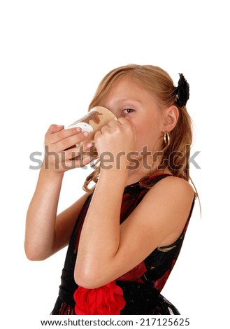 A blond young girl drinking from a cup in a nice dress, isolated for white background.  - stock photo