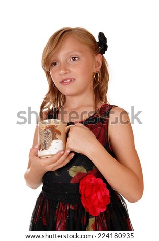 A blond young girl holding a cup in a nice black dress, isolated for white background.  - stock photo