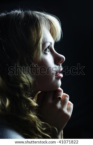 A blond young woman looking up - stock photo