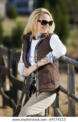 A blonde female with horses in an equestrian environment - stock photo