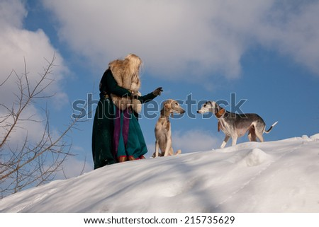 A blonde girl and grey and white salukies on snow  - stock photo