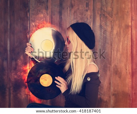 A blonde hipster girl with glasses is holding a vintage vinyl record for a music entertainment concept.