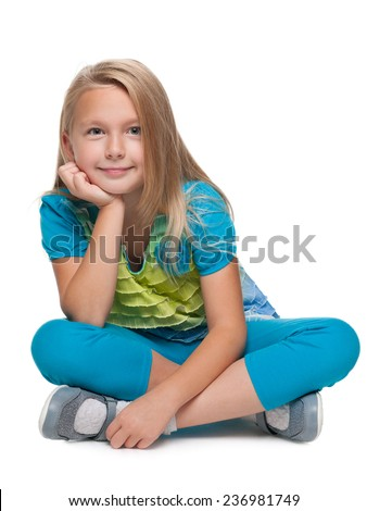 A blonde little girl is sitting on the floor on the white background - stock photo