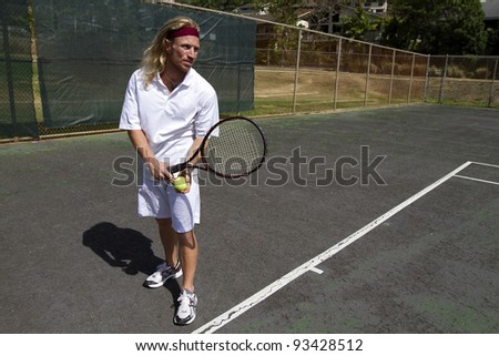 A blonde male tennis player gets prepared to make a strong overhand serve over the net - stock photo