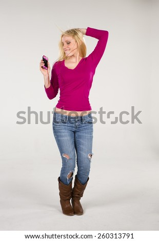 A blonde model enjoying music on an mp3 player - stock photo