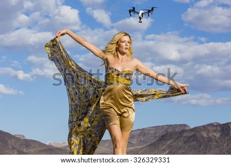 A blonde model posing in a desert environment with a drone in the background - stock photo