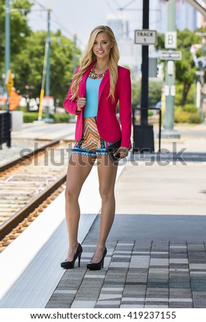 A blonde model using public transportation in a city environment - stock photo