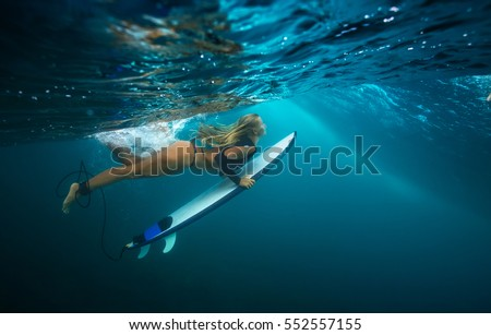 A blonde slim girl doing duck dive under blue wave. Water ripples under ocean surface. Water Sport activity in vacation. Sea fun lessons and beachlife lifestyle.