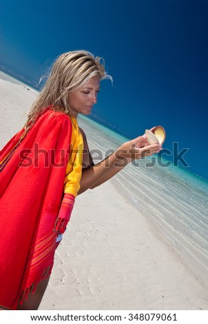 A blonde woman in bright red fabric playing with a beautiful sea shell - stock photo
