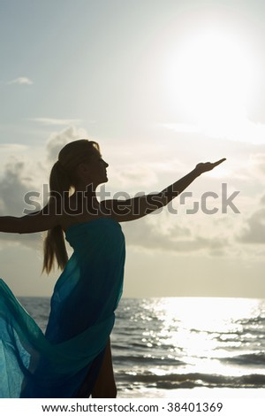 a blonde woman in profile standing at the water in a sheer dress is reaching up to catch the sun in her hand - stock photo