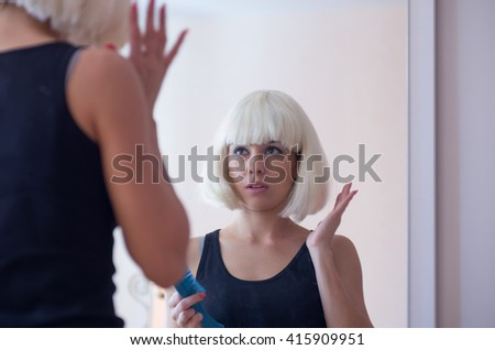 A blonde woman with a bob haircut standing front of a mirror with a hairbrush - stock photo