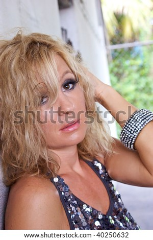 A blonde woman with big brown eyes is looking at viewer and seems very tired. - stock photo