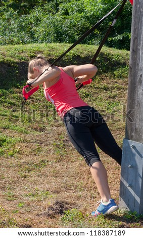 A blonde women makes fitnes exercise with a band in the green - stock photo