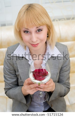 a blonde young caucasian woman holds a stemware with a red rose inside - stock photo