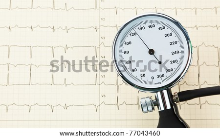 A blood pressure monitor and an ECG curve. Hypertension and heart disease