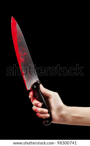 A bloody hand holding a large blood covered knife on a black isolated background. - stock photo