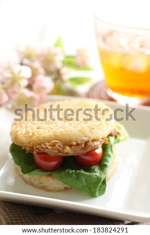 A BLT sandwich with buns made of rice-cakes with two cherry tomatoes and lettuce served on a white plate. - stock photo