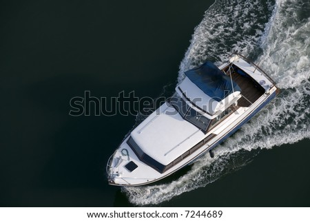 A blue and white cabin cruiser, with a wet canopy, shot from above while leaving harbour. - stock photo