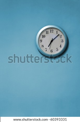 A blue and white clock on a blue wall - stock photo
